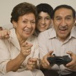 Hispanic grandparents playing video games with grandson — Stok fotoğraf