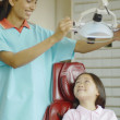 Indian female dental assistant with Asian girl in dentist's chair — Stock Photo