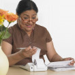 Senior Hispanic woman paying bills — Stock Photo