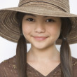 Studio shot of young Hispanic girl with hat — Stock Photo