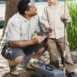 African father and son with fishing gear - Stock Photo