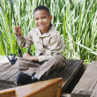 Young African boy on dock with fishing pole — Stock Photo