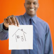 African man holding up napkin with house drawn on it - Stock Photo