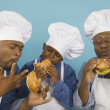 Multi-generational African male family members in chef's hats eating hamburgers — Stock Photo