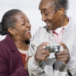 Senior African couple with digital camera smiling at each other — Stock Photo