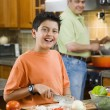 Hispanic father and son cooking and chopping vegetables in kitchen — Stock Photo
