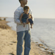 African father holding baby at beach — Stock Photo