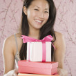 Young Asiwomsmiling with stack of gifts — Stock Photo #23254258