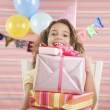 Young girl holding stack of gifts at birthday party — Stock Photo