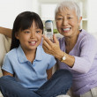 Asian grandmother and granddaughter looking at cell phone on sofa — Stock Photo #23254290
