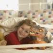 Young boy smiling in bed with toy dinosaur — Stock Photo