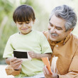 Father and son looking at photographs outdoors — Stock Photo