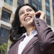 Indian businesswoman using cell phone outdoors — Stock Photo