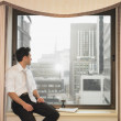Businessman sitting in window and looking out - Stock Photo