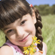 Young Hispanic girl holding flowers outdoors — Stock Photo