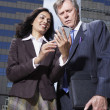 Businesswoman and businessman looking at PDA in urban scene — Stock Photo