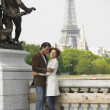 African couple hugging with Eiffel Tower in background — Stock Photo