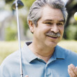 Middle-aged man with golf club and golf ball — Stock Photo