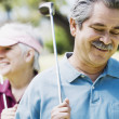 Middle-aged couple with golf clubs — Stock Photo