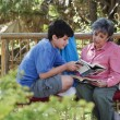 Hispanic grandmother and grandson reading outdoors — Stock Photo