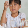 Young Asian girl with science equipment - Stockfoto