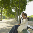 African couple sitting on park bench smiling — Stock Photo