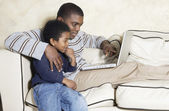 African American father and young son with laptop on sofa — Stock Photo
