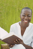 African American woman reading book outdoors — Stock Photo