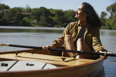 Woman sitting in canoe holding oar — Stock Photo