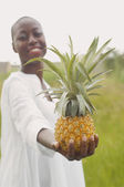 African American woman holding pineapple outdoors — Stock Photo