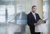 Businessman with newspaper leaning on glass wall — Stock Photo