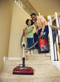 African father and daughter vacuuming stairs — Stock Photo