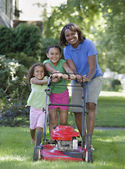 African mother and young daughters pushing lawn mower — Stock Photo