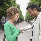 African couple looking at map in park — Stock Photo