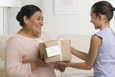 Hispanic girl giving gift to grandmother — Stock Photo