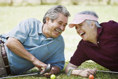Middle-aged couple laughing with golf clubs — Stock Photo
