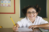 Hispanic girl doing schoolwork in classroom — Stockfoto