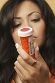 Young Hispanic woman looking at medication bottle — Stock Photo