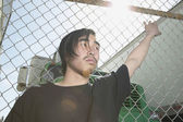 Young Asian man leaning against metal fence — Stock Photo