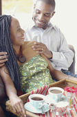 African American couple smiling with coffee tray — Stock Photo