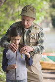 Hispanic grandfather helping granddaughter with fishing pole — Stock Photo
