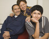 Hispanic grandparents and grandson smiling indoors — Stock Photo