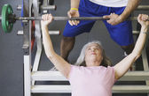 Male personal trainer with female client lifting weights — Stock Photo