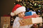 Hispanic girl holding gifts in front of Christmas tree — Stock Photo