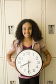African girl holding clock in front of lockers — Stock Photo