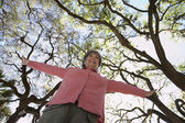 Low angle view of senior woman with arm outstretched outdoors — Stock Photo