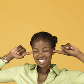 Studio shot of African woman plugging ears with fingers — Stock Photo