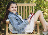 Girl sitting outdoors with book — Stock Photo
