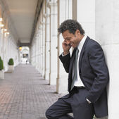 Businessman using cell phone in outdoor walkway — Stock Photo