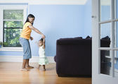 African mother and young daughter dancing in livingroom — Stock Photo